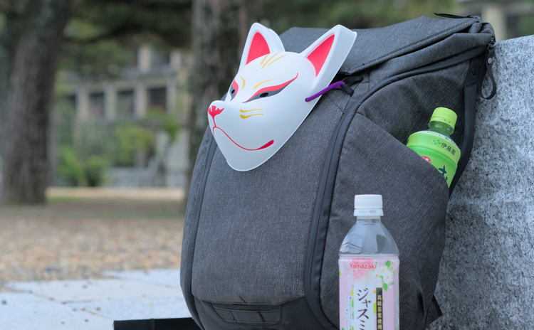 Kitsune mask attached to a backpack.